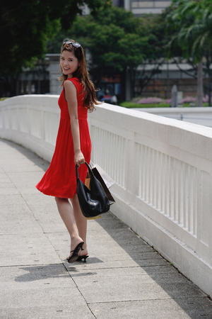over the shoulder: Woman in red dress carrying shopping bags, looking over shoulder LANG_EVOIMAGES