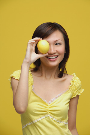 Young woman holding lemon over her eye