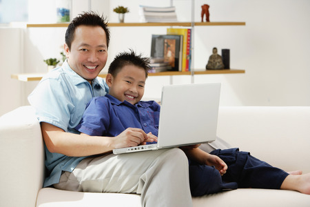 9 10 years: Father and son in living room with laptop, smiling at camera