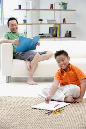 9 10 years: Father sitting on sofa, son on floor with drawing pad