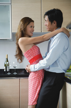 Couple at home, embracing in kitchen
