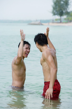waist deep: Two men standing in sea, giving high fives LANG_EVOIMAGES