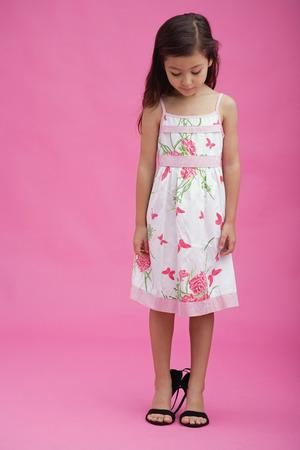 niños vistiendose: Young girl wearing high heel shoes, looking down