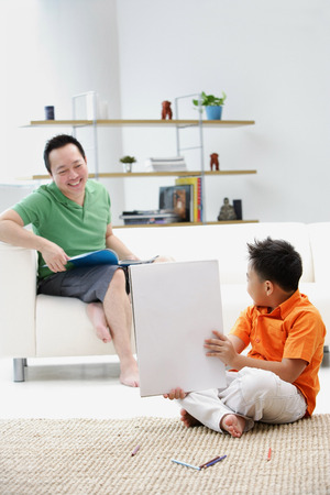 9 10 years: Father sitting on sofa, son on floor holding up drawing pad