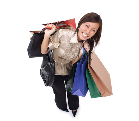 Woman carrying shopping bags, smiling up at camera