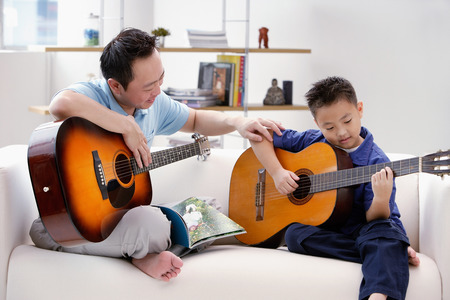 9 10 years: Father teaching son to play the guitar