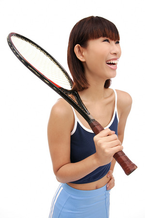 Young woman holding tennis racket over shoulder, smiling Stock Photo