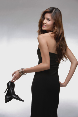 Woman in black dress, holding high heeled shoes, looking over shoulder