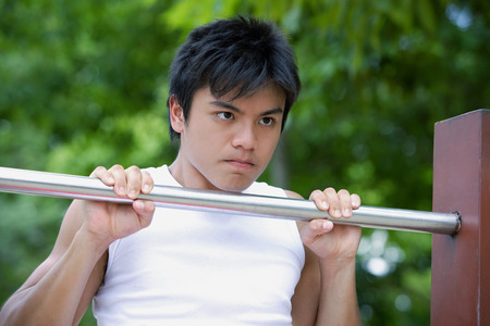 Young man doing chin-ups Stock Photo