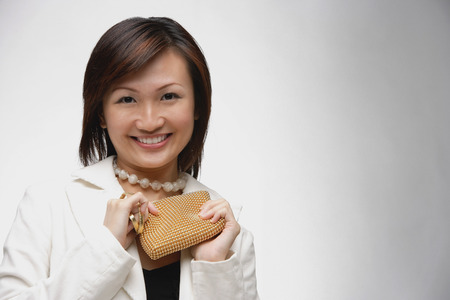 Young woman holding purse, smiling at camera Stock Photo