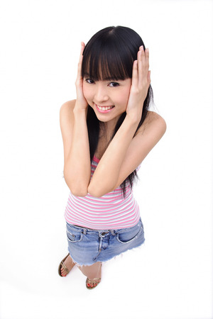 Young woman with hands over ears, looking at camera LANG_EVOIMAGES