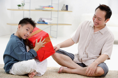 9 10 years: Father and son at home, boy holding big gift box