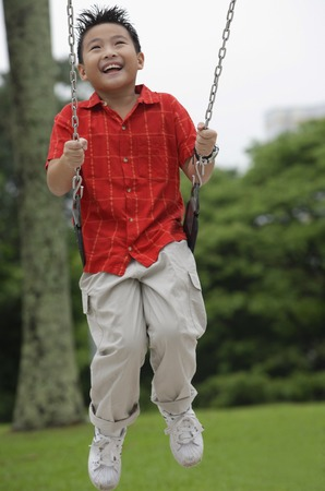 9 10 years: Boy on playground swing, smiling