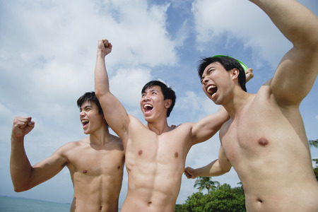hombres sin camisa: Three shirtless men raising fists LANG_EVOIMAGES