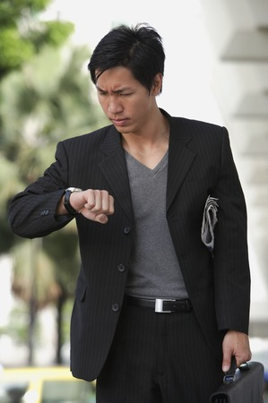 Businessman holding briefcase, looking at watch, frowning Stock Photo