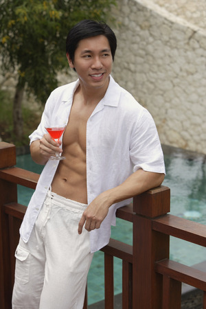 fully unbuttoned: Man leaning on railing, holding cocktail