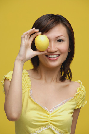 Young woman holding lemon over her eye, portrait