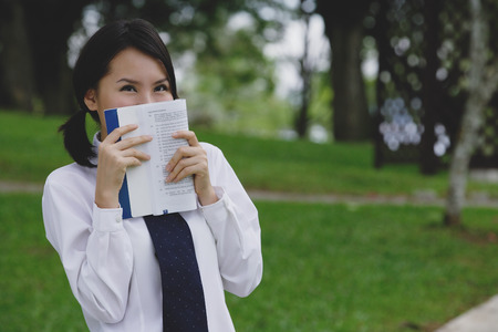covering face: Young woman in school uniform, book covering face LANG_EVOIMAGES