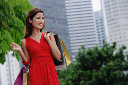 Woman in red dress carrying shopping bags, city location
