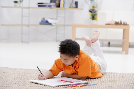 9 10 years: Boy lying on floor with sketch pad LANG_EVOIMAGES