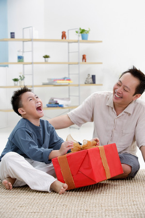9 10 years: Father and son at home, boy opening gift, looking up LANG_EVOIMAGES