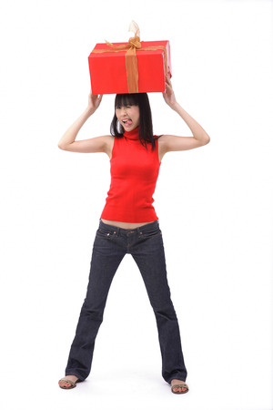 Young woman balancing big red gift box on her head Stock Photo