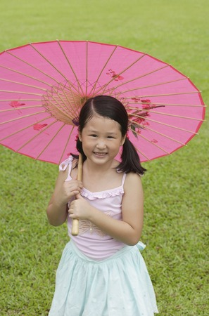 Girl using pink traditional Chinese paper umbrella Stock Photo