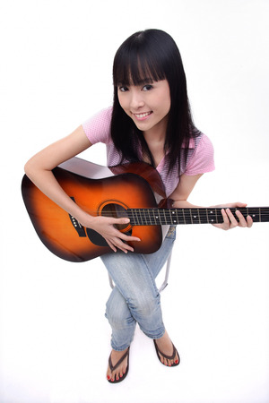 Young woman with guitar, smiling at camera