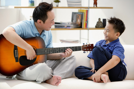 9 10 years: Father and son sitting on sofa, father playing guitar