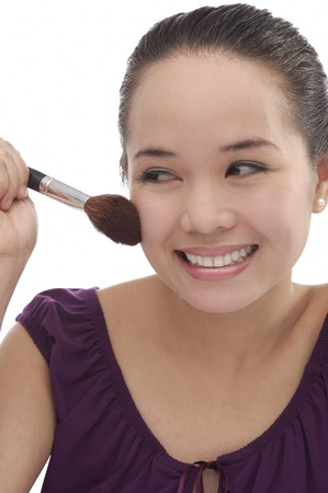 Young woman applying make-up Stock Photo