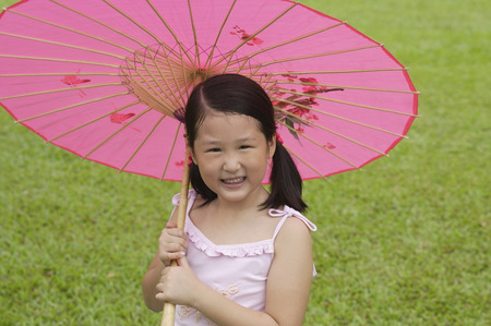 paper umbrella: Girl using pink traditional Chinese paper umbrella, looking at camera LANG_EVOIMAGES