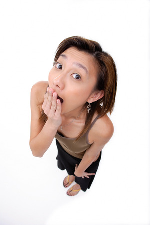 Young woman covering mouth, looking at camera Stock Photo