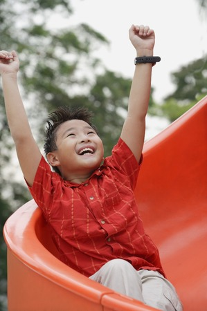 9 10 years: Boy coming down playground slide, arms outstretched, smiling, looking up LANG_EVOIMAGES