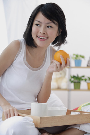 Young woman having breakfast in bed, holding orange, looking away