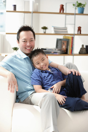 9 10 years: Father and son in living room, smiling at camera, portrait