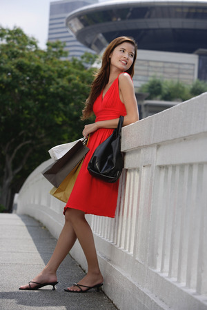 Woman with shopping bags, leaning on railing, looking away