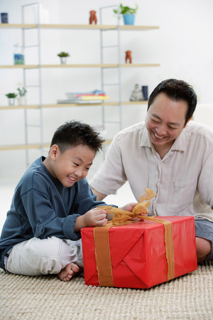 9 10 years: Boy opening gift box, father next to him LANG_EVOIMAGES