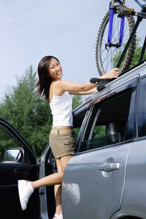 Woman standing on car, securing bike on top of car