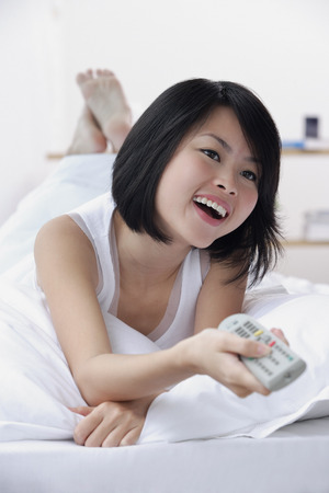 wasting away: Young woman with TV remote control, smiling