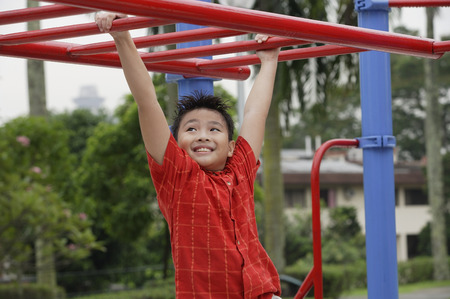 Boy using the jungle gym at playground