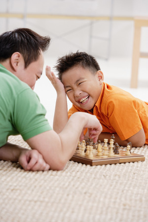 9 10 years: Father and son lying on floor, playing chess, son laughing LANG_EVOIMAGES