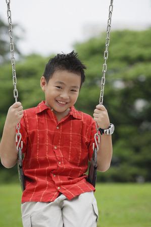 Boy on swing, smiling at camera