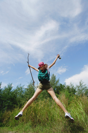 Female hiker, jumping, arms outstretched Stock Photo