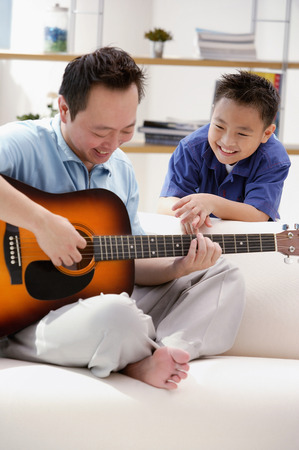 Father playing the guitar, son watching him Stock Photo
