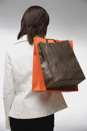 rearview: Woman carrying shopping bags, rearview