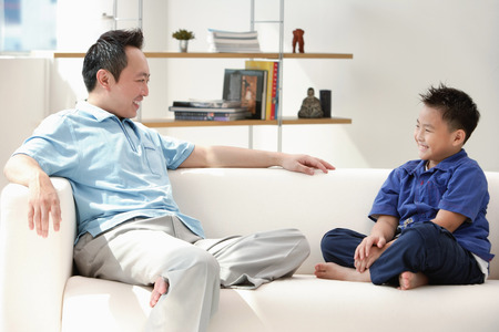 9 10 years: Father and son sitting on sofa, smiling at each other