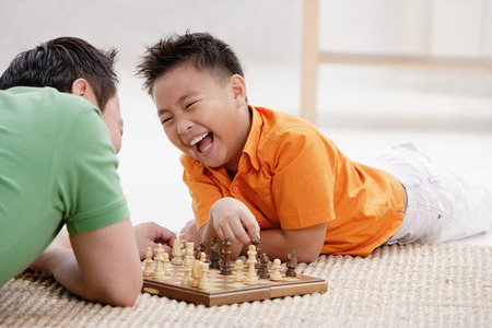 9 10 years: Father and son lying on floor, playing chess, laughing LANG_EVOIMAGES