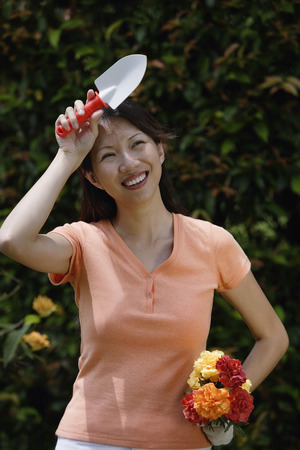 Woman holding trowel and bouquet of flowers, wiping her brow Stock Photo