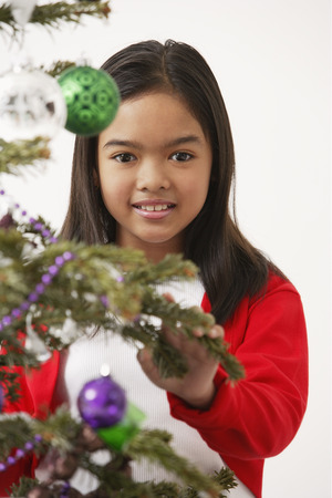 Girl by the Christmas tree, looking at camera
