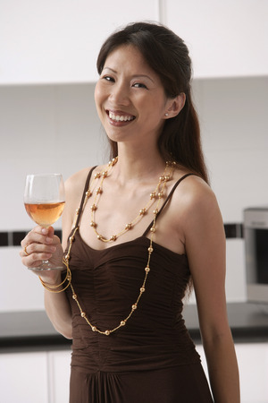 Woman in kitchen holding glass of wine, smiling at camera Stock Photo